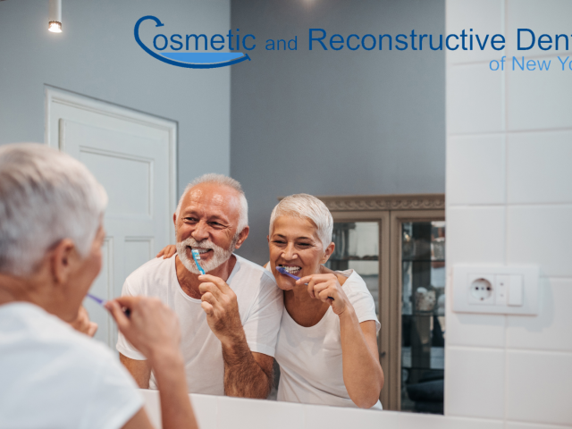 Older couple together looking at mirror while brushing teeth for a perfect smile - Dr. Jessica Pandich, DDS