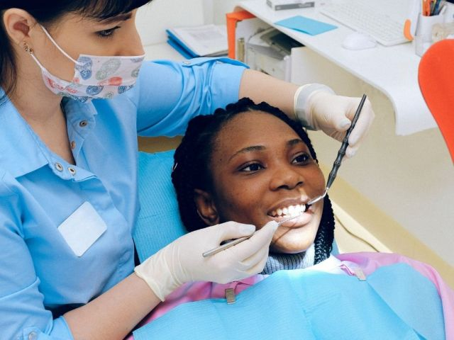 Woman having a dental deep cleaning in dentists office - Jessica Pandich, NY